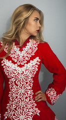 Irish dancer in red competition costume with her hand on her hip