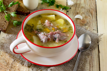 Delicious soup with rice and chunks of meat, rye bread on a wood