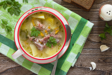 Delicious rice soup with pieces of meat and rye bread on a woode