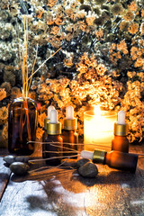 Bottles of organic aromatherapy essential oils with dry flowers