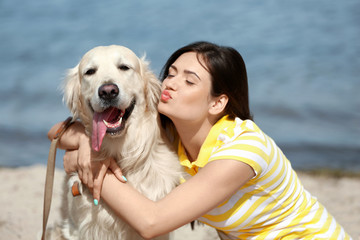 Beautiful girl with cute retriever on river shore