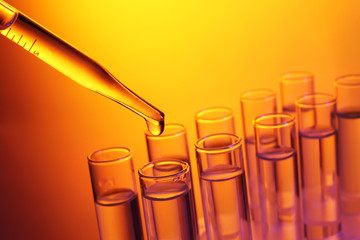 Close up of a pipette dropping a  sample into a test tube on colourful background