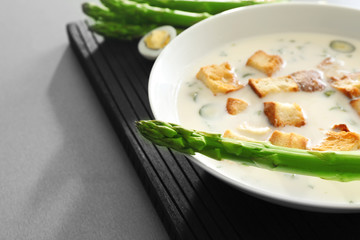 Tasty asparagus soup with crackers on table