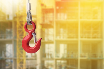 Red lifting crane hook on construction site with lighting effect
