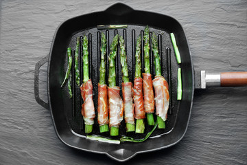 Asparagus with bacon on frying pan