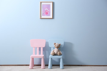 Two children chairs with toy on blue wall background