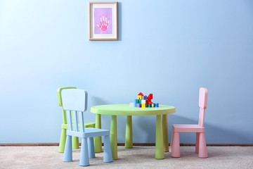 Children furniture with toys on blue wall background