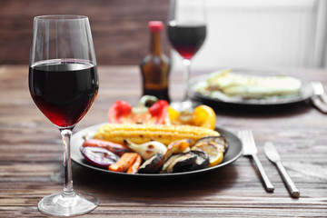 Grilled vegetables and glass of wine on wooden table