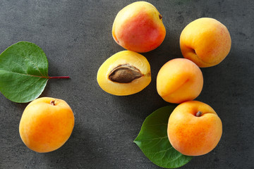 Fresh juicy apricots on grey table
