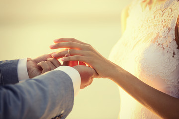 Groom and bride hands on sunset background
