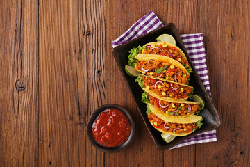 Tacos with meat and vegetables on wooden board