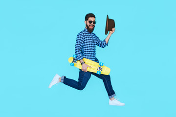 Pretty young bearded man jumping with yellow skateboard