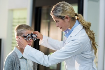 Female optometrist examining young patient with phoropter