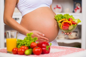 Close-up of a pregnant belly. Women's Health, fortified food. Fresh vegetables, diet and figure