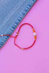 Bracelet red thread and blue jeans on a pink background. fashionable jeans top view