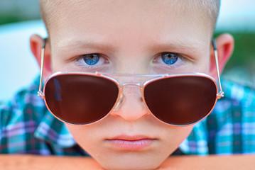 portrait of boy close up in sunglasses