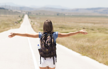 Woman backpacker walking on road Wall mural