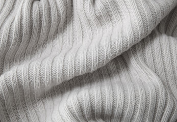 A full page close up of cream knitted jumper fabric texture