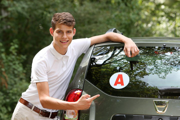 Young man leaning on a car
