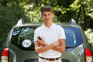 Young man leaning on a car with key