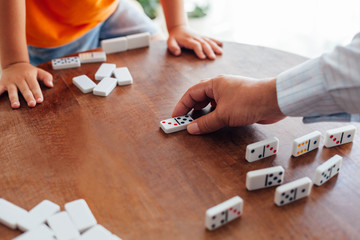 Senior man playing dominoes with kid