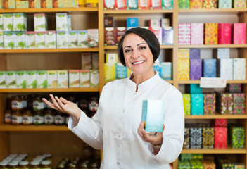 Woman in white coat promoting food additive goods in carton in d