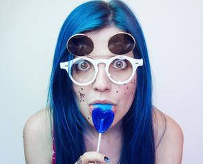 Chica joven con el pelo azul lamiendo una piruleta azul