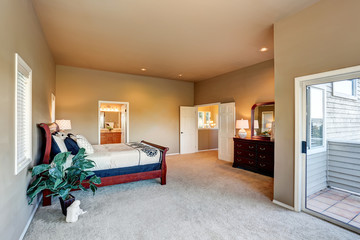 Spacious bedroom interior with beige walls and wooden furniture.