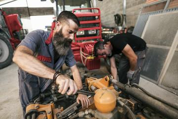 Mechanic working in workshop with tractors
