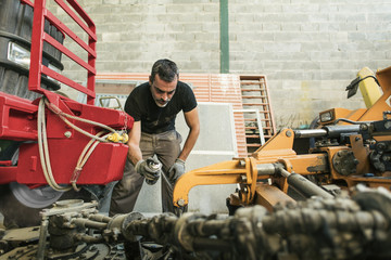 Mechanic maintaining tractor
