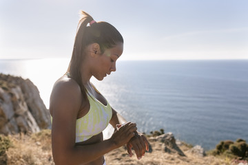 Spain, Asturias, sportswoman on the coast, looking at the smartwatch