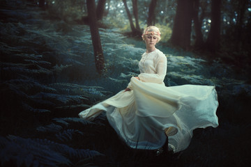 Ethereal woman dancing in dreamy forest