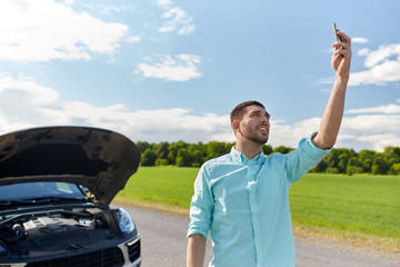 man with smartphone and broken car at countryside