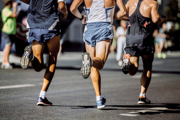 legs male runners running through streets of city during marathon