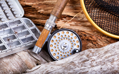 Vintage fly fishing outfit and gear on rocks and wood background