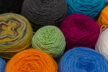 Many small balls of wool  rainbowcolors on the wooden table.