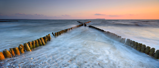 Coastal Sunset on the Baltic Sea, X-shaped  Wooden Groynes, long exposure, Rügen Island, Germany Wall mural