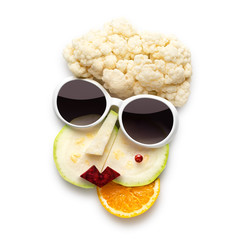 Tasty art / Quirky food concept of cubist style female face in sunglasses made of fruits and vegetables, isolated on white.