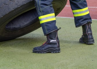 Protective boots of a firefighter./ Look at the legs of a fireman in protective boots and pants with reflective tapes.