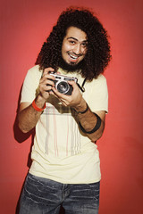 Happy photographer laughing with beautiful long curly hair holdi