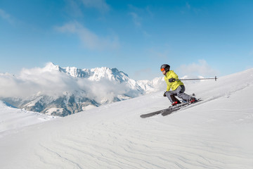 Alpine skier with snowy mountains