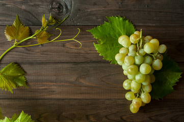 bunch of green grapes with leaves on the wooden background