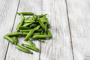 green peas pods on a white wooden table