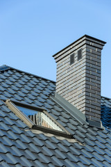 Roof of a detached house with a skylight and chimney against the
