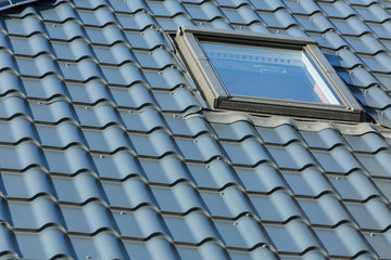 Roof of a detached house with a roof window against the sky