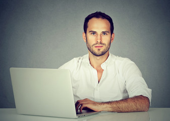 Smiling young business man using a laptop