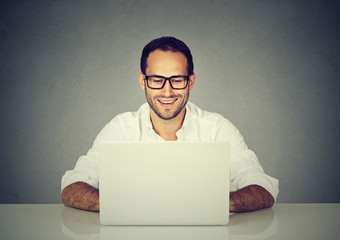 Happy man working sitting at desk, looking at laptop computer