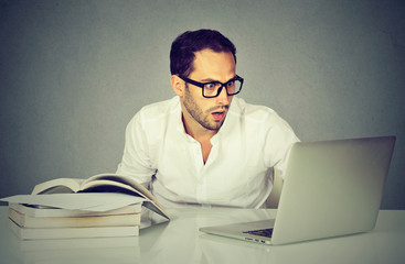 young surprised business man working with laptop