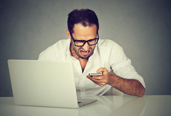 Frustrated man with laptop texting on his mobile phone