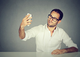 young funny looking man taking pictures of him self with smart phone